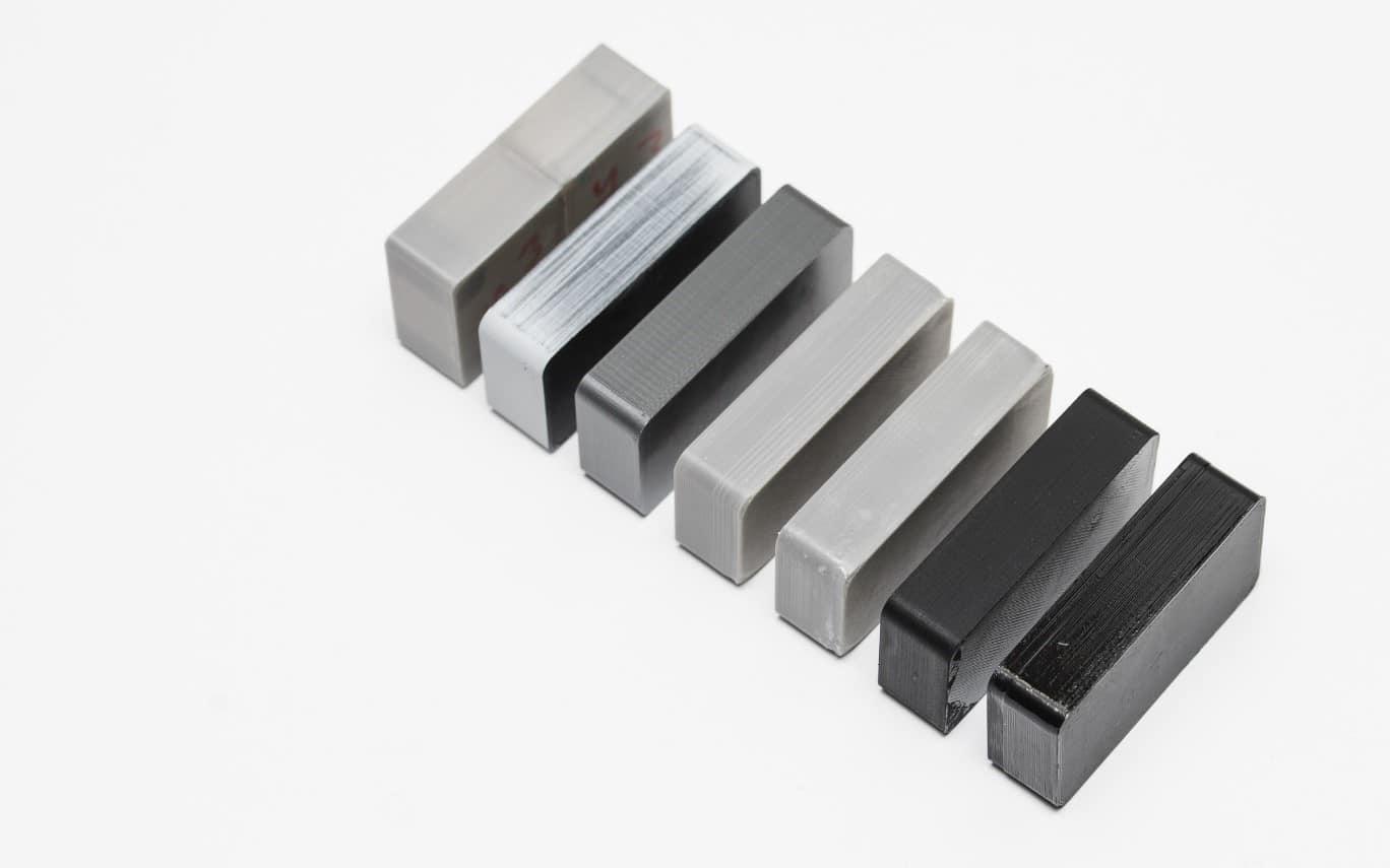 مقایسه قطعات تولید شده توسط پرینتر سه بعدی FDM با انجام روش های مختلف پرداخت سطح و پولیش (از چپ به راست) : اتصال سرد - پرکردن شکاف ها - قطعه پرداخت نشده - سنباده شده - پولیش شده - رنگ شده - پوشش اپوکسی داده شده