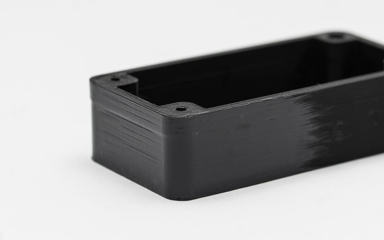 یک قطعه پرینت سه بعدی شده مشکی رنگ از جنس ABS را مشاهده میکنید که دیوارههای آن توسط ایجاد پوشش اپوکسی پرداخت شده است و سطح بالایی آن بدون پرداخت میباشد